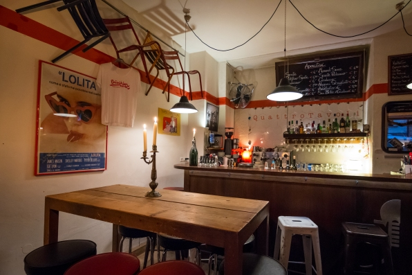 Man sieht ins innere des Quattro Tavoli, im Hintergrund die Bar und die Fliesen, davor ein Tisch und vier Stühle an der Wand. Alte Filmposter und Kerzenlicht sorgen für eine gemütliche Atmosphäre